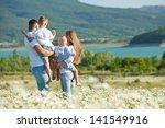 happy family having fun outdoors | Shutterstock . vector #141549916