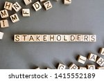 Small photo of the word stakeholder wooden cubes with burnt letters, business development in favor of shareholders gray background top view, scattered cubes around random letters