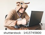 Office worker in cosplay costume of a cow. Guy in the funny animal pyjamas sleepwear near the laptop. Parody on manager.