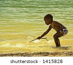 Young African American child playing with a stick in the water. - stock photo