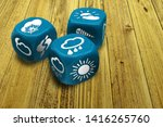 Small photo of Wrong weather forecast concept poster. Inexact methods of prediction. Three dices with weather condition symbols on faces. Macro of blue gambling cubes on wooden table background
