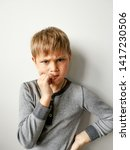 Small photo of Thoughtful worried young boy biting his nails in trepidation as he stares at the ground with a serious expression, profile head shot