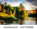 Stock photo a scenic lake or river during a light rain displaying a rainbow in the mist on an autumn day close 141729688