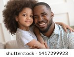 Small photo of Happy affectionate african american family young daddy and small cute child daughter portrait, loving black dad and little mixed race kid girl bonding embrace looking at camera on fathers day concept