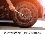 Small photo of Man Tighten the car wheel nut