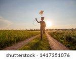 A Little Boy Starts A Kite At...