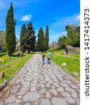 People walks on stone path of ancient Roamn road Via Appia Antica in big park area in Rome, Italy