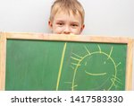 boy drawing sun with crayons on ... | Shutterstock . vector #1417583330