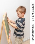 boy drawing with crayons on... | Shutterstock . vector #1417583336