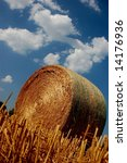 Golden hay ball with blue sky and white clouds - stock photo