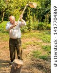 Senior Man Splitting Wood With...