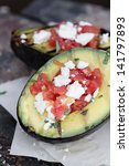 Grilled avocados filled with diced tomatoes and feta cheese and garnished with olive oil and freshly chopped parsley.