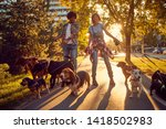 Stock photo outdoor with dogs smiling couple walking and enjoying in the park 1418502983