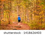 Small photo of Overweight woman in blue tank walking briskly in woods in fall