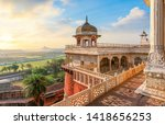Small photo of Agra Fort - Medieval Indian fort made of red sandstone and marble with view of dome at sunrise. View of Taj Mahal at a distance as seen from Agra Fort.