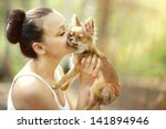 Stock photo woman playing with a small dog 141894946