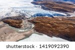 Greenlandic ice sheet melting glacier into river with tundra aerial view, near Kangerlussuaq, Greenland