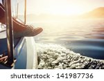 feet on boat sailing at sunrise ... | Shutterstock . vector #141987736