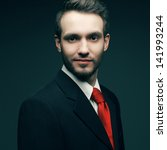 Portrait of a young handsome man (businessman) in black suit with trendy red tie smiling and looking at camera. Trendy beard (bristle). Close up. Studio shot - stock photo