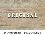 Small photo of Letter block in word original on wood background
