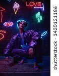 Small photo of Cyberpunk style portrait of girl in futuristic purple sportswear. She poses against wall of neon figures. Set is lit with magenta light. Clothes is oversized