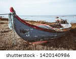 An old peeling colorful wooden rope-bound fishing boat on the grass of the river bank with a horizon,  waterscape and a few other boats behind in a defocused background, Alcochete, Portugal