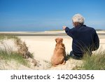 Stock photo man sitting with dog on sand dune at dutch beach on wadden island texel 142043056