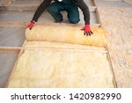 Work composed of mineral wool insulation in the floor, floor heating insulation , warm house, eco-friendly insulation, a builder at work - stock photo