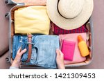 Woman Traveler Packing Clothes...