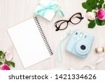 Modern polaroid camera, gift box, glasses, feminine accessories, roses on wooden background. Top view, tender minimal flat lay style composition. Women desk, fashion blogger, beauty technology