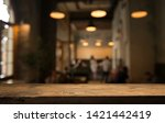 Stock photo image of wooden table in front of abstract blurred background of resturant lights 1421442419