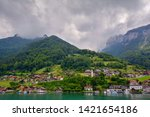 Beautiful view to Merligen, Switzerland in Swiss Alps located on Lake Thun (Thunersee) shore from tourist boat under the dramatic cloudy sky