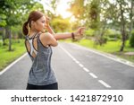 Small photo of Fitness woman doing stretch exercise stretching her arms - tricep and shoulders stretch wearing a smartwatch activity tracker. Women stretching for warming up before running or working out.