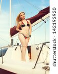Portrait of a gorgeous long-haired blonde in stylish swimsuit standing on the aft of a sailing yacht. Sunny summer day. Bikini fashion. Outdoor shot - stock photo