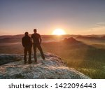 Hikers and friends stay on cliff within dreamy daybreak and thinking. Dreamy fogy landscape blue misty sunrise in a beautiful valley below