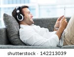 man on sofa with headphones and ... | Shutterstock . vector #142213039