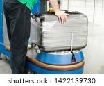 Small photo of Worker wraps suitcase with a transparent film before travel by airplane for security reason and safety protection from damage. Additional packing of baggage at the airport terminal