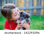 Stock photo children girl kissing her puppy chihuahua doggy on the wood fence 142291096