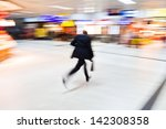 running man in the shopping passage of a railway station in motion blur - stock photo