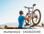 mountain biker man take of his... | Shutterstock . vector #1423623140