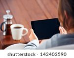 young woman uses tablet while... | Shutterstock . vector #142403590