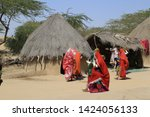 Small photo of Tharparkar Sindh, Pakistan - March, 2019: People of Thar Village gathered in colourful dress outside their rural house huts, Man Woman families preparing to sit outside their houses, Poor Huts