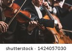 Small photo of Professional symphonic string orchestra performing on stage and playing a classical music concert, violinist in the foreground