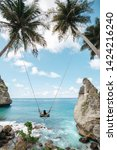 Small photo of Young girl swinging on a swing overlooking the blue sea. Travel adventure on paradise tropical island. A young girl swinging on a swing between palm trees on the beach of a tropical island