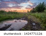 Summer landscape at sunset. Dirt road with a large puddle , which reflects the sky, goes into the field. The field is covered with fog against a blue-orange sky and gray clouds. Russia