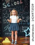 Small photo of Little blonde girl with a surprised face with a ruler in her hands Pupil girl with big rulers against chalkboard with school formulas. back to school. Schoolgirl learning geometry. math lesson