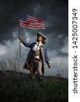 Small photo of American revolution war soldier with flag of colonies over dramatic landscape. 4 july independence day of USA concept photo composition: soldier and flag.