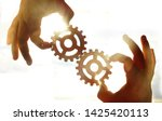 Small photo of Male hand holding two wooden cog gear wheel on sunny sky background. sunshine and yellow and yellow sky . sun rays.one part of whole. symbol of association and connection. business strategy