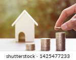 Small photo of Property investment, home loan, reverse mortgage, Business and financial concept. A man hand putting coin on pile coins with burred small house model on wooden table.