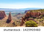 Fruita Canyon, is a steep canyon lined with towering Wingate sandstone walls. Rim Rock Drive snakes up the canyon below before climbing its west side. The canyon floor is composed of 1.5-billion-year-